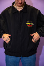 Load image into Gallery viewer, Black in colour, this zip-up jacket has a 'Snap On Racing' spell-out in yellow and red on the left chest and a yellow spell-out down the left sleeve. On the back is a large similar looking spell-out with a large 'S' in red in the middle and gold flags protruding upwards.