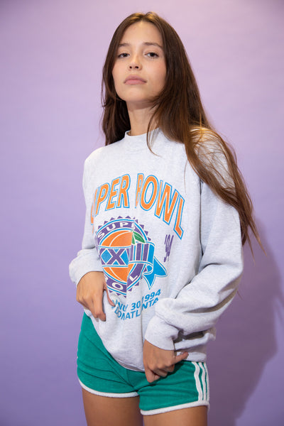 Grey in colour, this jumper has a large orange and blue 'Super Bowl' spell-out across the top with a large Super Bowl emblem below. Dated 1994