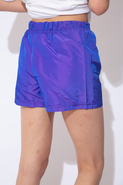 the model wears a reflective purple pair of shorts