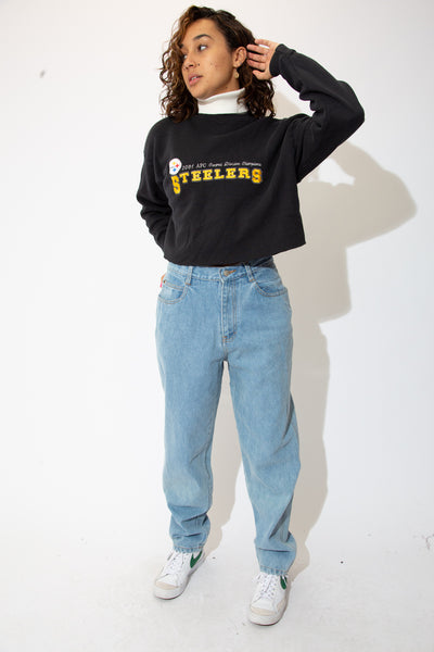 the model wears a black cropped sweater with steelers graphic