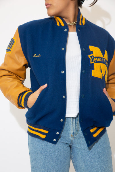 the model wears a navy and brown leather letterman jacket