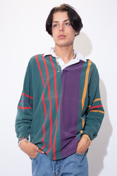 Vertically striped in dark green, red, purple and yellow, this rugby style sweater has a white collar with matching white buttons.