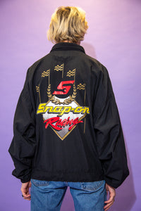 Black in colour, this zip-up jacket has a 'Snap On Racing' spell-out in yellow and red on the left chest and a yellow spell-out down the left sleeve. On the back is a large similar looking spell-out with a large 'S' in red in the middle and gold flags protruding upwards.