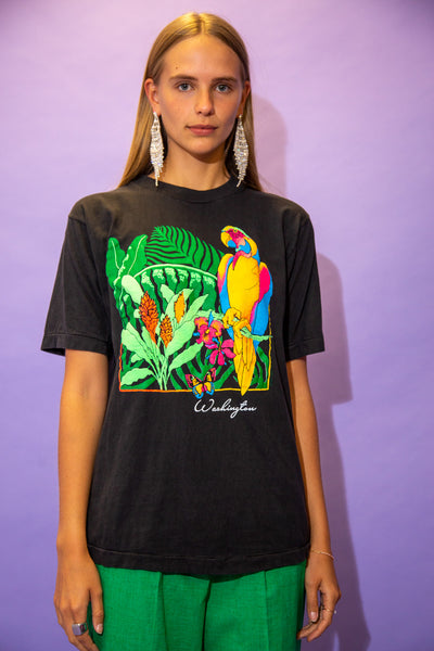 the model wears a faded black tee with a parrot graphic on the front
