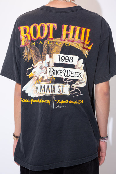 Faded black oversized tee with a small pocket on the left breast that reads 'Boot Hill Saloon 1998 Bike Week' and a large Boot Hill Saloon & Eagle graphic across the back of the tee. Daytona Beach Bike Week, also called Daytona Bike Week, is a motorcycle event and rally held annually in Daytona Beach, Florida. Approximately 500,000 people make their way to the rally area for the 10-day event. The tee would look epic with a pair of cowboy boots and faded black denim!