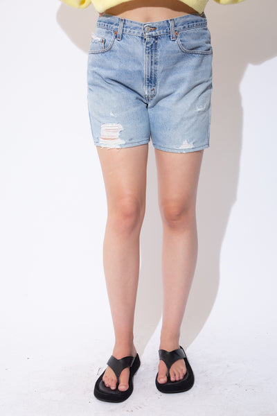 Light wash denim shorts with light brown stitching, Levi's branding on the button, domes and back waistline and distressing across the pockets and legs.