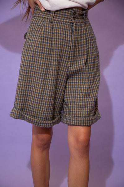 Soft in feel, these tailored shorts are in a brown and blue plaid design with folded rims and double button closures
