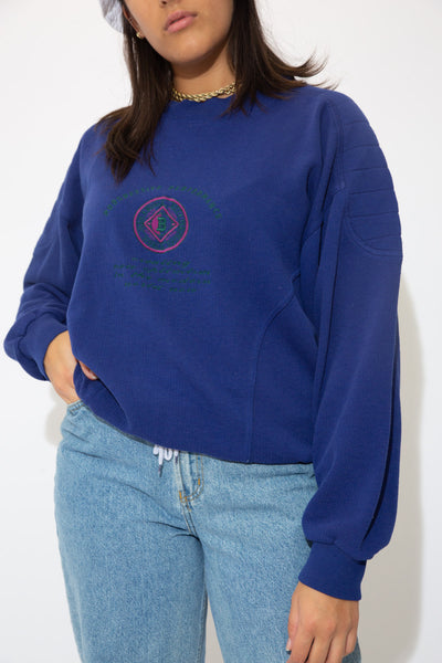 the model wears a sweater with a bugle boy graphic