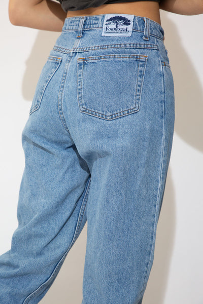 the model wears a pair of mid blue wash jeans