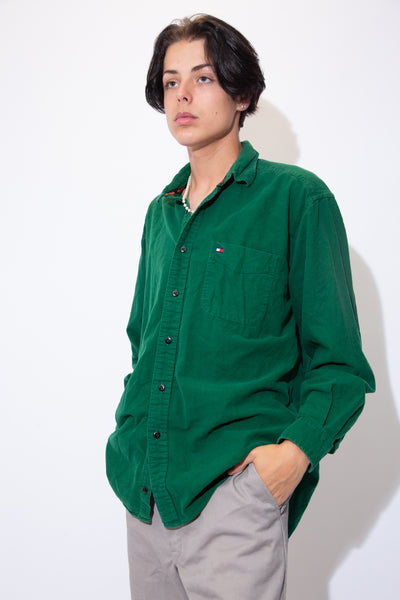 Make your friends green with envy in this Tommy Hilfiger Button-Up! Soft dark green button-up with full-length black buttons and a Tommy Hilfiger logo on the left chest pocket.