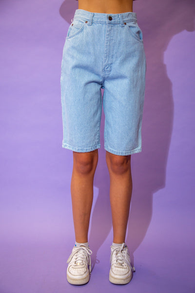 the model wears a pair of long light blue denim shorts