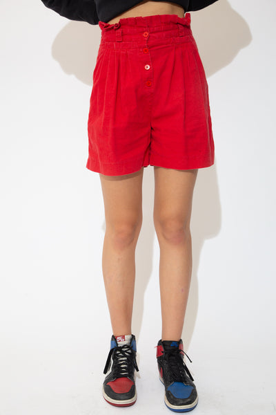 Red shorts in a high-waisted pleated style with four closing buttons, double pockets and belt loops.
