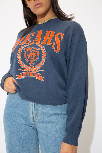the model wears a navy chicago bears sweater