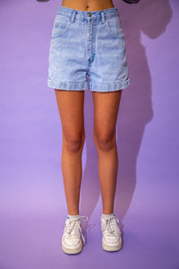 the model wears light blue wash denim shorts