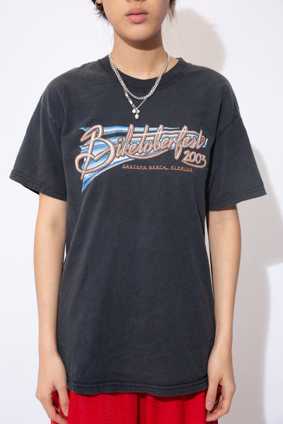 the model wears a faded black tee with biketoberfest graphic on front and back