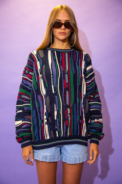 The model wears a multi coloured coogi style sweater