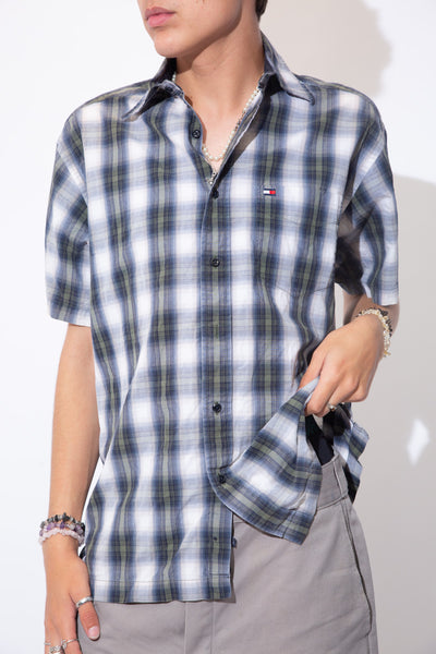 Short sleeved button-up shirt in a blue, green and white plaid print with full length navy blue buttons and Tommy Hilfiger branding on the left chest pocket.