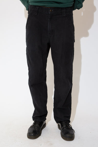 the model wears a pair of faded black carhartt pants