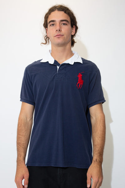 Navy blue rugby style tee with a white collar, white buttons and a large red embroidered Ralph Lauren logo on the left chest.