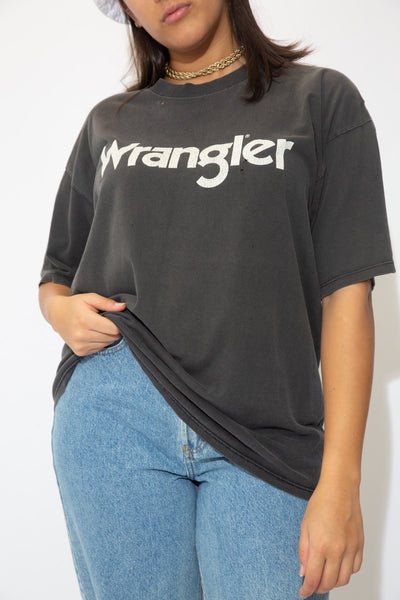 the model wears a faded black tee with wrangler spell out