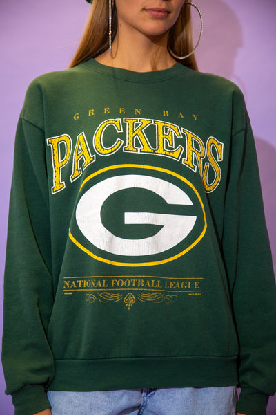 the model wears a forest green sweater with a green bay packers spell out on the front