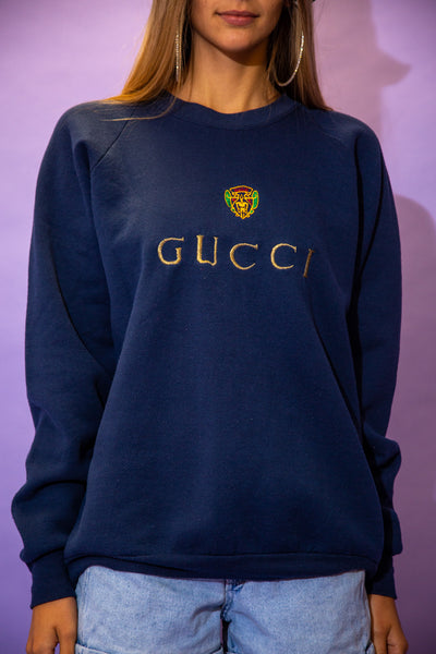 the model wears a navy sweater with a gucci spell out