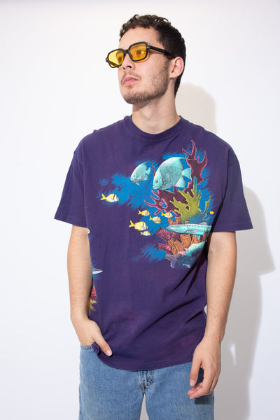 the model wears a purple tee with an allover fish print