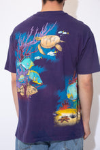Load image into Gallery viewer, the model wears a purple tee with an allover fish print