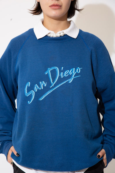 the model wears a san diego spell out sweater