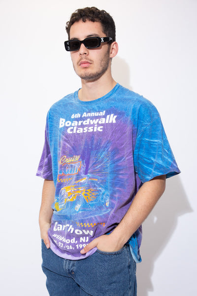 Blue and purple tie-dye tee with a flaming car print on the front and '6th Annual Boardwalk Classic' printed above in white. 'Cruise Night' printed below in colour and dated 1999.