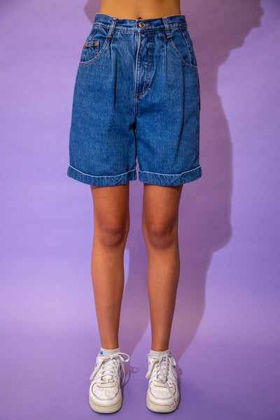 the model wears a pair of mid blue wash denim shorts