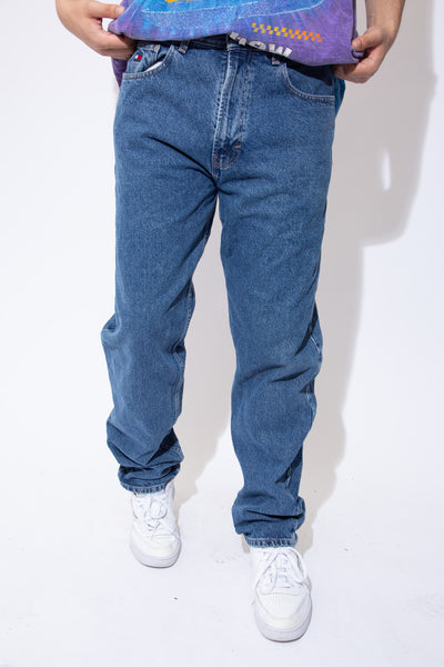 Mid-wash blue denim jeans in a straight to tapered leg fit with brown stitching and Tommy Hilfiger branding on the button, front right pocket, domes and back waistline.