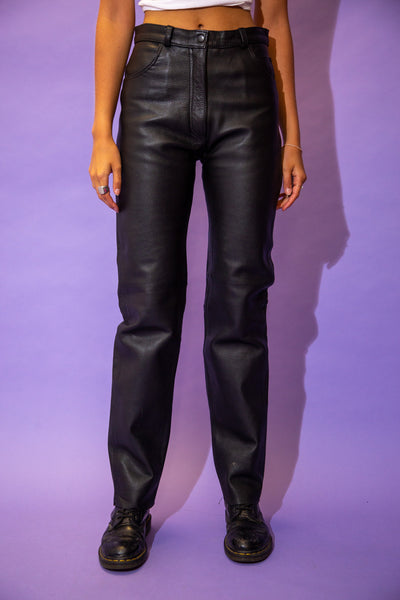 the model wears a pair of black leather pants