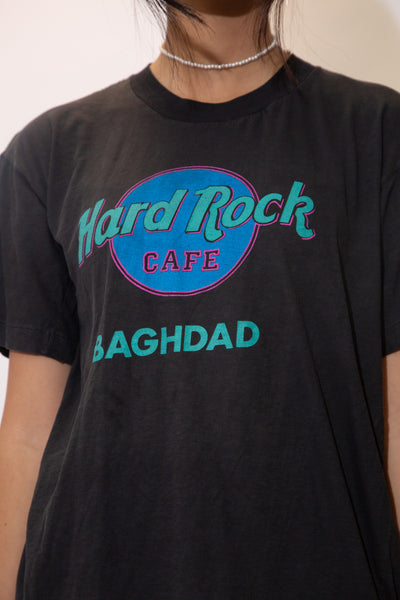 the model wears a faded black tee with a hard rock baghdad spell out