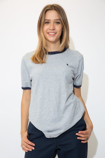 Grey tee in a ringer style with a navy blue rimmed neckline, rimmed sleeves and a navy blue embroidered Ralph Lauren logo on the left chest.