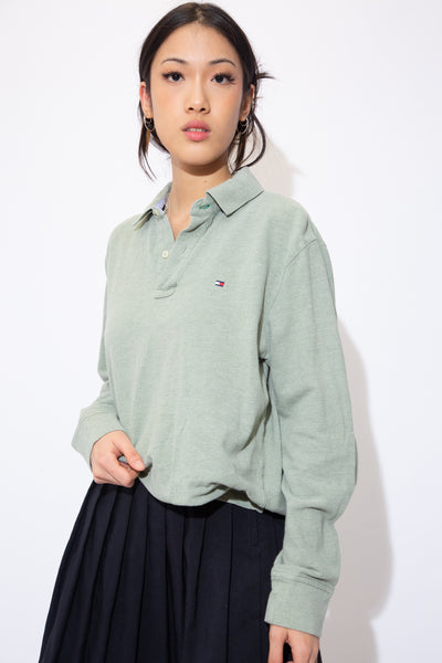Pale green polo-style sweater with white buttons and the Tommy Hilfiger logo on the left chest.