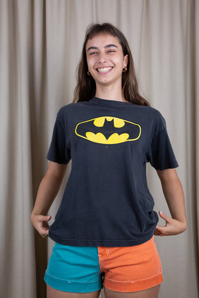 the model wears a faded black tee with a batman logo