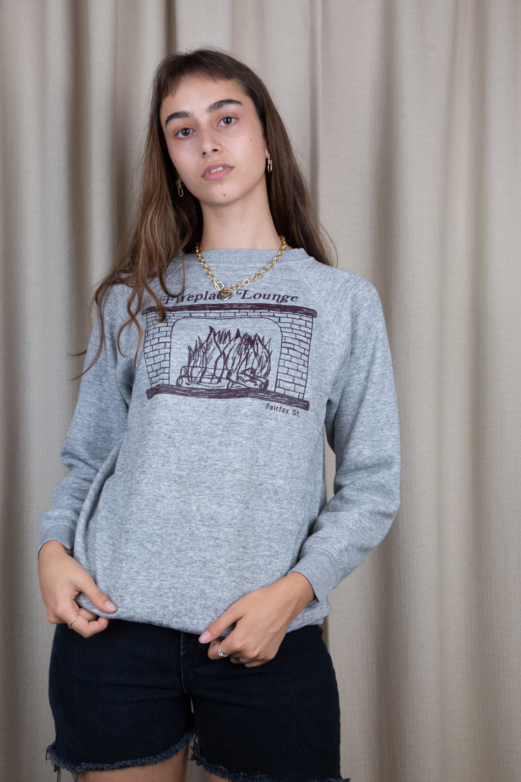 the model wears a grey sweater with a fireplace lounge graphic