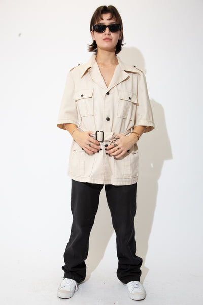Light brown in colour, this short sleeve trench coat has four large pockets with contrast black buttons and a tie-around strap.