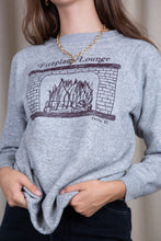 Load image into Gallery viewer, the model wears a grey sweater with a fireplace lounge graphic