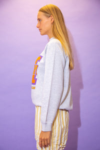 the model wears a grey sweater with a 'coach' graphic on the front