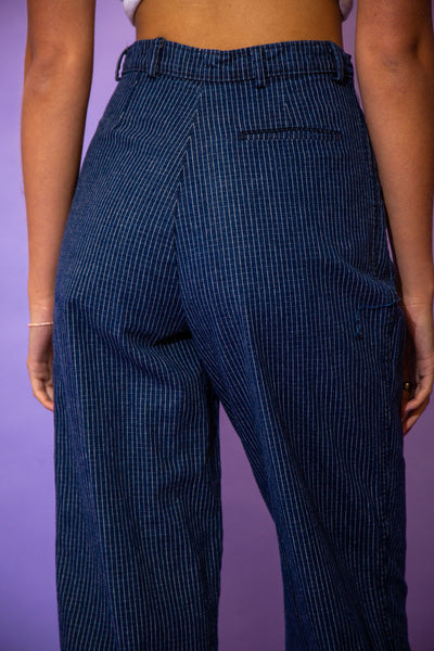 the model wears a pair of pinstripe denim pants