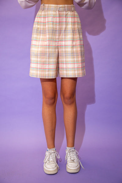 the model wears a pair of flowy tartan shorts