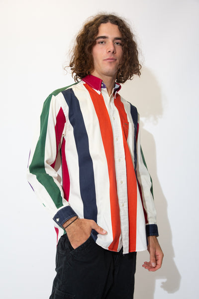 White button-up shirt vertically striped in red, blue, green and orange. Finished off with the Tommy Hilfiger lion emblem below the left chest pocket.