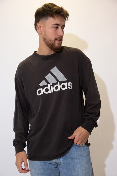 Black long sleeved tee with white and grey Adidas branding on the front.