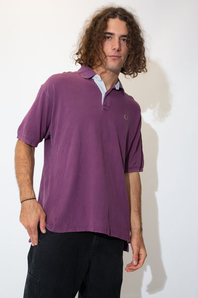 Purple polo style tee with a ribbed feel, light blue and white striped neckline, white buttons and the Tommy Hilfiger lion emblem on the left chest.