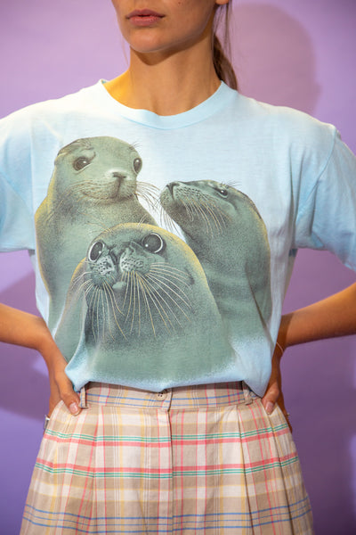 the model wears a blue tee with a seal graphic