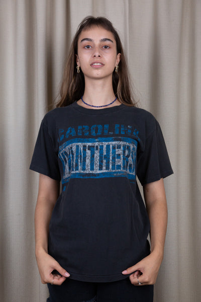 the model is wearing a faded black carolina panthers tee