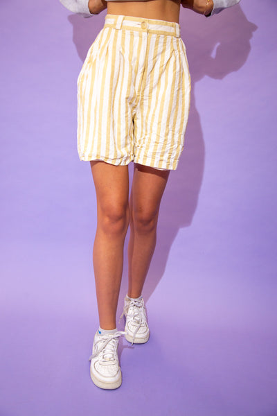 the model wears a pair of striped yellow and cream shorts