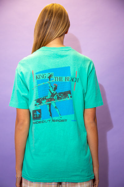 the model wears a turquoise tee with a volleyball graphic on the back